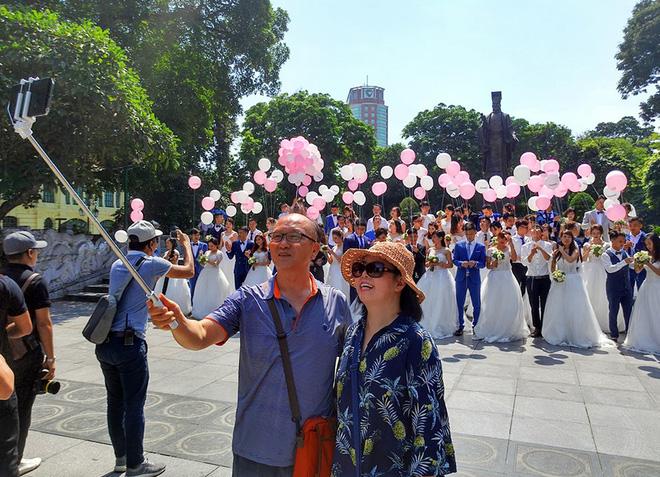 Nhiều vị khách ngoại quốc thích thú selfie trước cảnh 40 cặp đôi xúng xính váy áo.