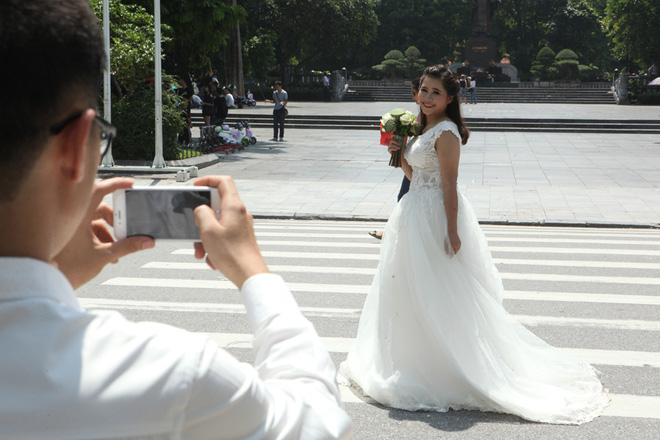 Chú rể chụp ảnh cho cô dâu giữa phố đi bộ quanh Hồ Gươm.