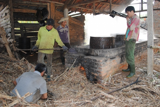 Một gia đình ở Tân Hương nhen lò nấu mật mía (ảnh Duy Ngợi).