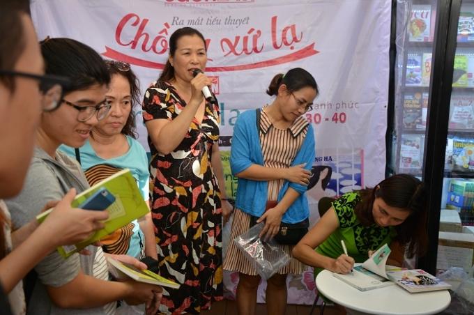 Nhà văn Trang Hạ ký tặng đọc giả cuốn sách tiểu thuyết Chồng xứ lạ của mình ra mắt hôm nay.