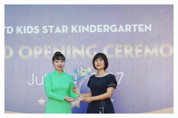 Bà Phan Thị Hải Yến trao biểu tượng cho Hiệu trưởng nhà trường Tô Thị Phương Bình