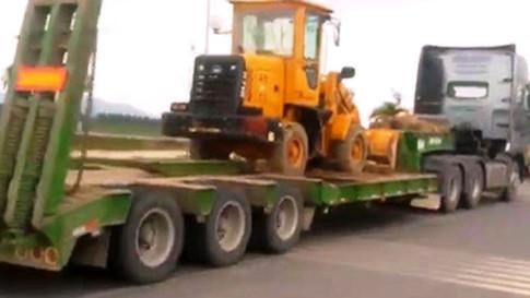 Chiếc xe đầo kéo chở theo máy ủi mini, gỗ, nhưng không hề có dây an toàn chằng buộc. (Ảnh: CSGT cung cấp).