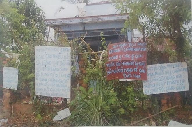 """Tấm bảng đề dòng chữ """"… Trước đổi mồ hôi để có đất, bây giờ đổi mạng để giữ đất + nhà"""" tại một căn nhà nay đã bị cưỡng chế. (Hình người dân xã Long Hưng cung cấp)."""