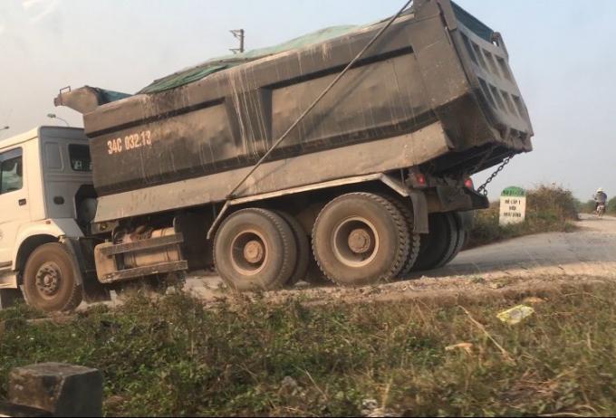 Những chiếc xe tải khác men theo con đường bê tông song song Quốc lộ 5, trèo lên đê để ra đường lớn.