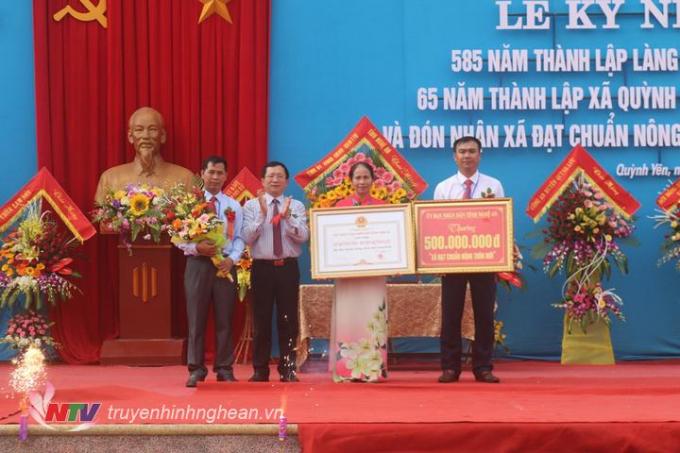 Đồng chí Đinh Viết Hồng trao bằng công nhận và một công trình phúc lợi trị giá giá 500 triệu đồng cho đại diện xã Quỳnh Yên có thành tích xuất sắc trong phong trào xây dựng NTM.