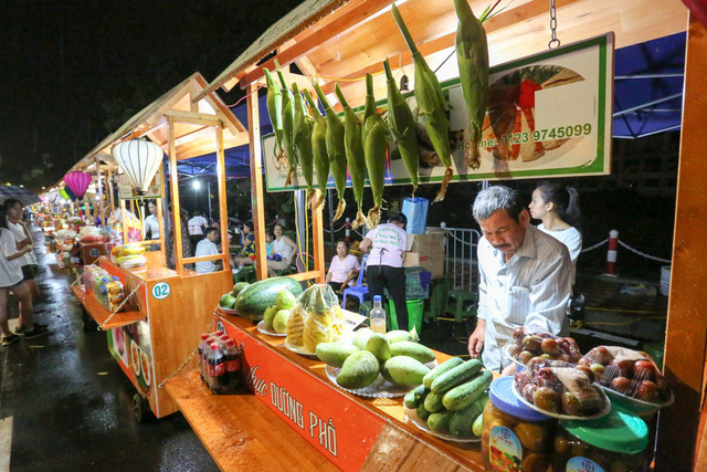 Một gian hàng bán hoa quả tươi trên phố đi bộ.