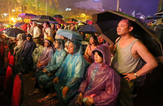 Người dân đứng theo dõi chương trình nghệ thuật dưới trời mưa.