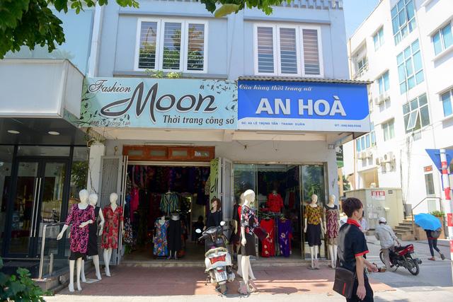 Một cửa hiệu thay biển mới, bên cạnh là tấm biển