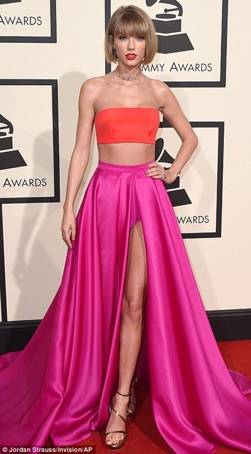 Taylor Swift vô cùng nổi bật trên thảm đỏ với chiếc váy màu hồng cắt xẻ sâu và chiếc áo ôm màu hồng cam khoe đường cong vòng 1 và vòng 2.