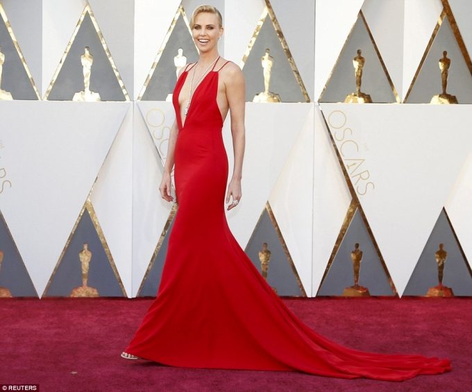 Charlize Theron hấp dẫn sải bước với chiếc đầm màu đỏ cắt xẻ sâu ở ngực khoe hững hờ vòng 1.