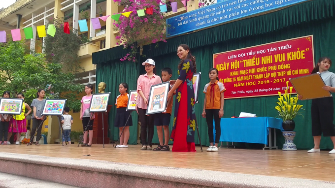Cô Nguyễn Thị Thanh Mai - Hiệu trường trường tiểu học Tân triều trao bức tranh cho bà Thu Hương (một phụ huynh học sinh) trong buổi đấu giá.