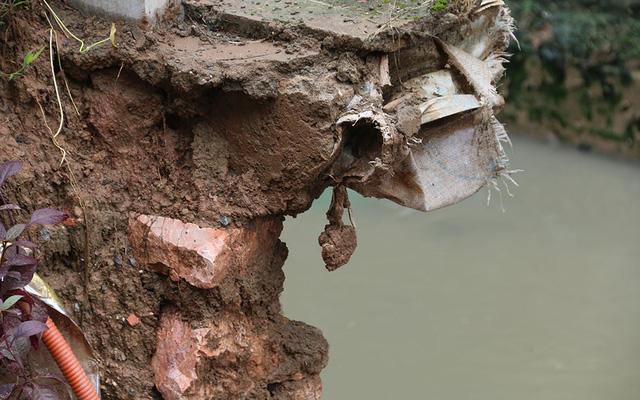 Phần đất đá tiếp tục sạt xuống mương thoát nước.