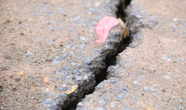 Nhiều vết nứt lớn và kéo dài xuất hiện trên đường nhựa ngay cạnh đoạn bị sạt lở.