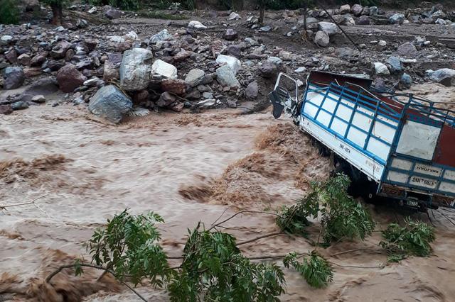Chiếc xe tải nằm bất động trên đường đi của một dòng lũ. Hai người trên xe hiện đang mất tích, nghi bị nước lũ cuốn trôi.