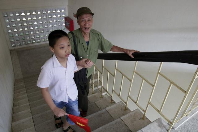 Ông Đặng Văn Vấn phấn khởi đưa cháu nội là bé Đặng Minh Hải 8 tuổi đến trường dự lễ khai giảng. Trường được thành lập vào năm 1977, khi ấy trường mang tên