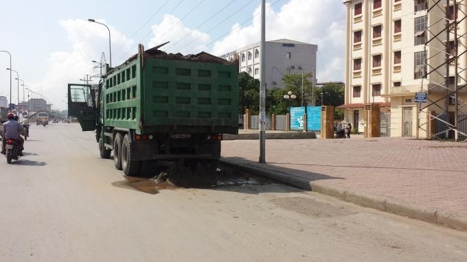 Xe tải để vương vãi vật liệu xây dựng tại chân cầu vượt Mai Dịch