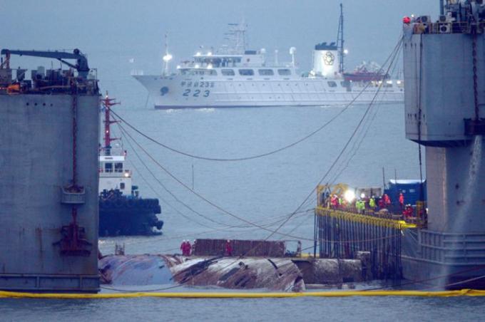 Hai chiếc xà lan bắt đầu tách dần nhau ra để tạo lực kéo phà Sewol lên. Ảnh: Reuters