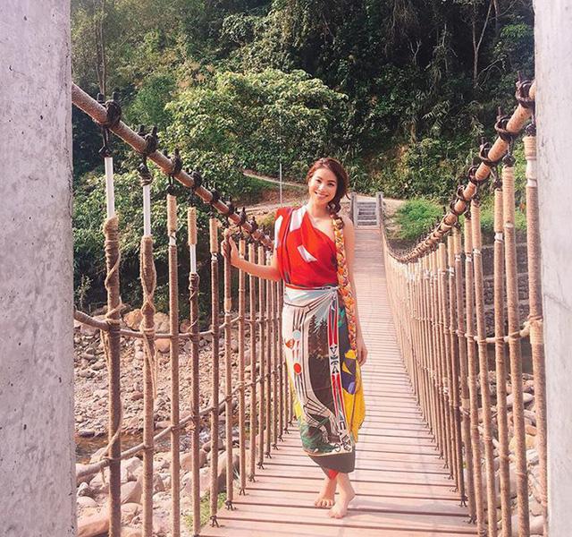 Hoa hậu Phạm Hương dùng khăn hàng hiệu làm váy quấn, đi chân trần lên cây cầu treo bắc qua sông ở Huế.
