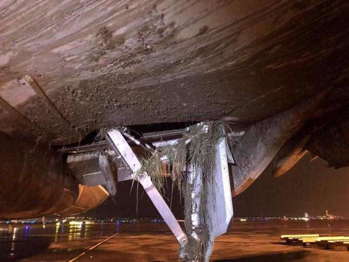 Phần càng và bụng máy bay Vietnam Airlines dính đầy bùn đất, cỏ cây vì hạ cánh lệch vị trí tại sân bay Nội Bài. Ảnh: CTV cung cấp.