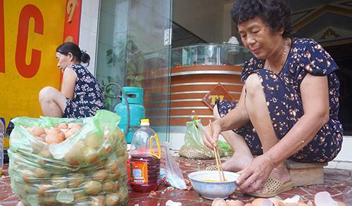 Bà Thìn (bên phải) đang nấu thức ăn bên chiếc bếp dã chiến trên vỉa hè. Ảnh:Lê Hoàng.