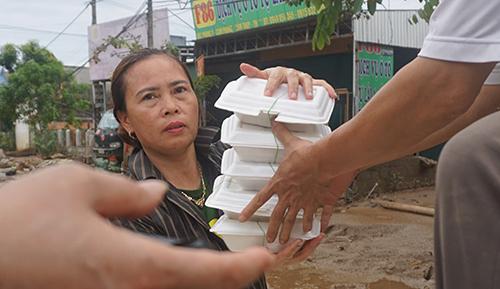 Đều đặn hai bữa mỗi ngày, người dân vùng lũ ở Cẩm Phongđược phát cơm miễn phí đến tận nhà, giúp họ qua cơn đói. Ảnh:Lê Hoàng.