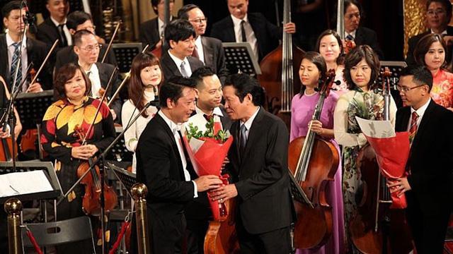 Thứ trưởng Hoàng Vĩnh Bảo tặng hoa chúc mừng nhạc trưởng Lê Phi Phi sau chương trình.