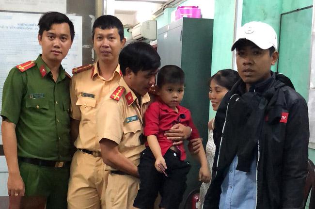 Lực lượng CSGT bàn giao cháu bé đi lạc lại cho gia đình.