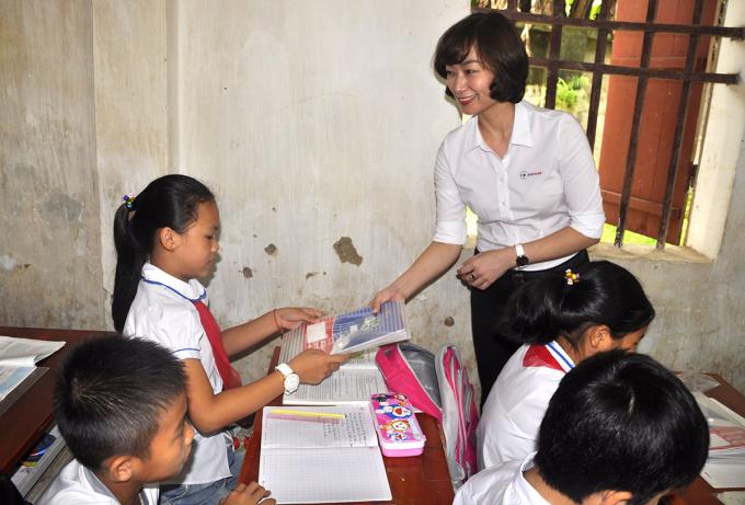 Đại diện EVN HANOI trao tặng những cuốn vở tới các em học sinh.