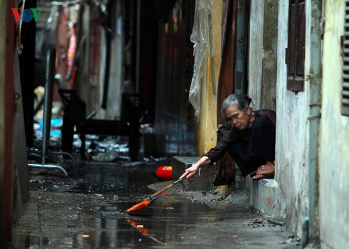 Bà Hoa Thị Tửu, sinh năm 1940 đang tranh thủ quét dọn trước cửa nhà, ngôi nhà của bà may mắn không bị ảnh hưởng nghiêm trọng trong vụ cháy.