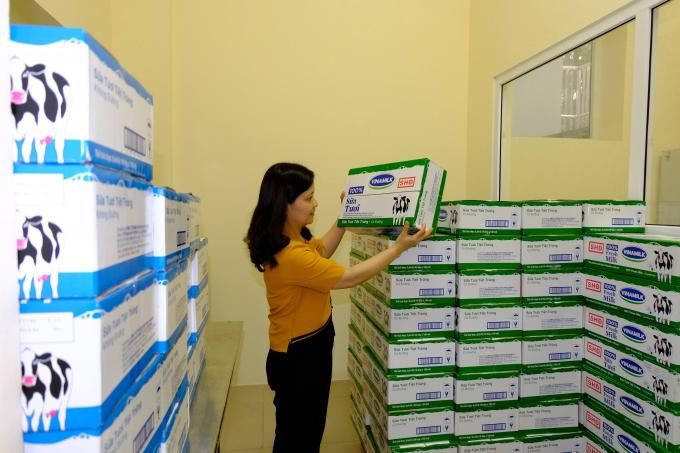 Cô giáo kiểm tra, chuẩn bị sữa học đường cho các em học sinh trước giờ uống sữa tại trường Mầm non Ánh Sao, Hà Nội
