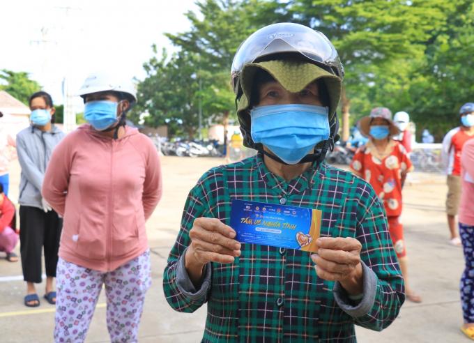 Bà Nguyễn Thị Hiền vui mừng cầm tấm vé để mua nhu yếu phẩm cho mình và con gái