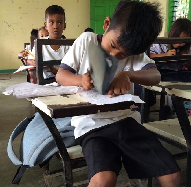 Harold dùng dép để tẩy vì không có đủ đồ dùng học tập. Ảnh: Rosalie Dela Cruz.