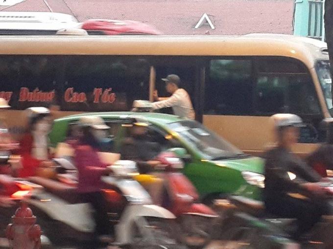 Phụ xe nhoài người ra ngoài, chèo kéo khách ngay giữa lòng đường.