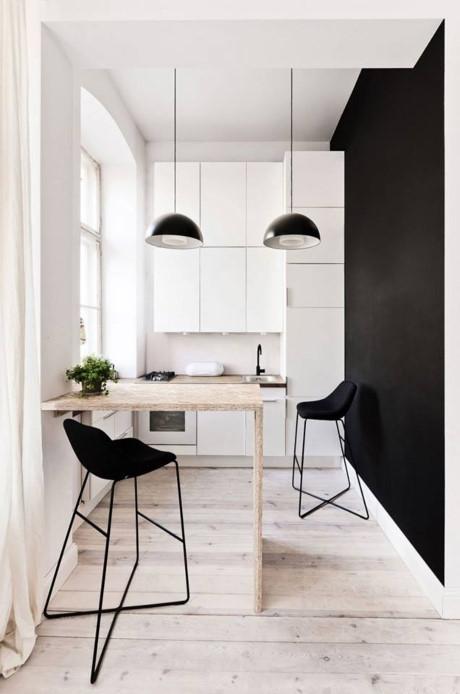 Khu vực bếp ăn thoáng sạch được bố trí kín đáo bên hông nhà. Một bức tường đen tương phản tạo không gian đặc biệt cho phòng bếp.
