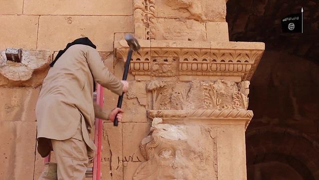 Một thành viên của IS phá bỏ những tượng cổ ở khu Hatra. (Ảnh: Dailymail).