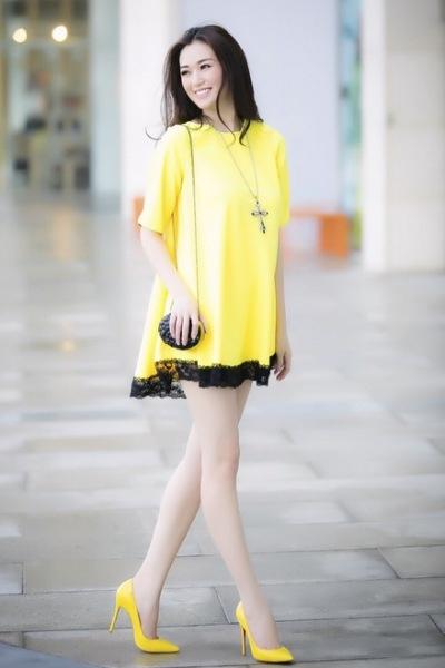 Chiếc váy màu vàng thêm phần ren màu đen, kết hợp với chiếc túi xách nhỏ màu đen trông bạn thật nổi bật và sành điệu. Ảnh: internet.