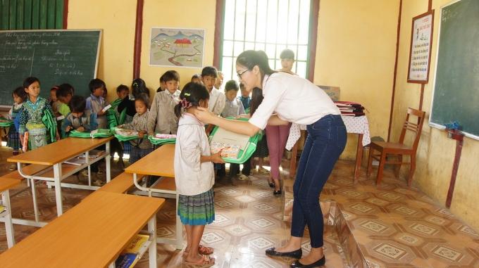 Diệu Ngọc trao cặp sách cho các em học sinh tiểu học.
