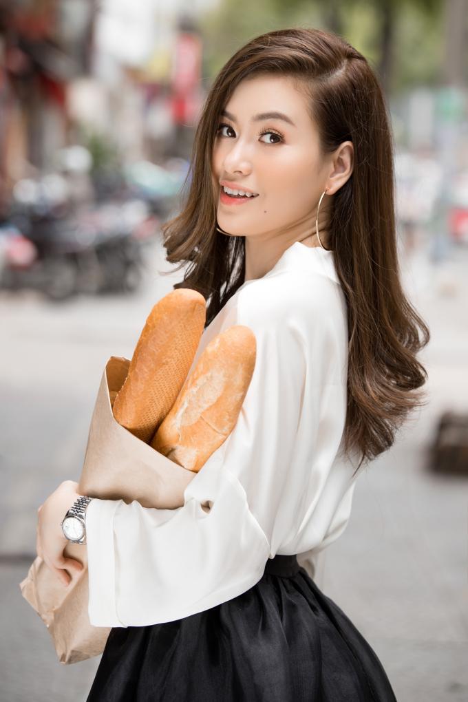 Trong những bức hình này, Hoa hậu Diễm Trần hóa cô gái bán bánh mỳ yêu kiều trên phố. Chiếc áo sơ mi dáng rộng kết hợp cùng chân váy kiểu công chúa càng làm tôn lên vẻ nữ tính và dịu dàng của nàng Hoa hậu.