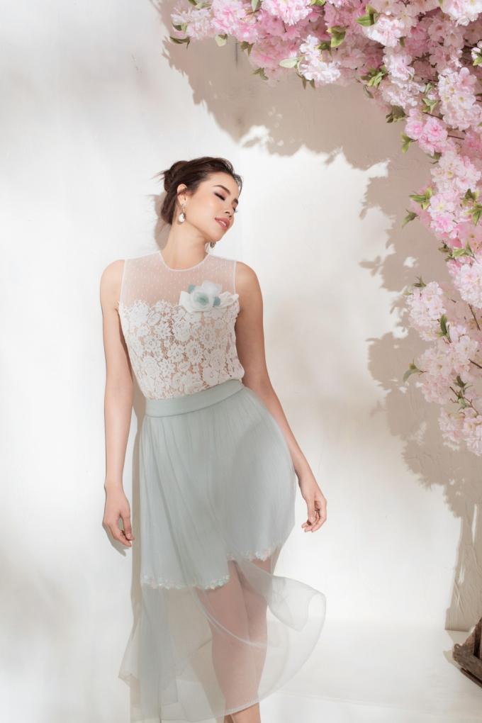 Cùng chân váy layer, bạn cũng có thể học hỏi Phạm Hương lựa chọn cách phối với phần thân màu trắng. Kỹ thuật đắp ren thủ công tiếp tục được thực hiện công phu, mang đến những đoá hoa trắng lãng mạn cho các cô gái.