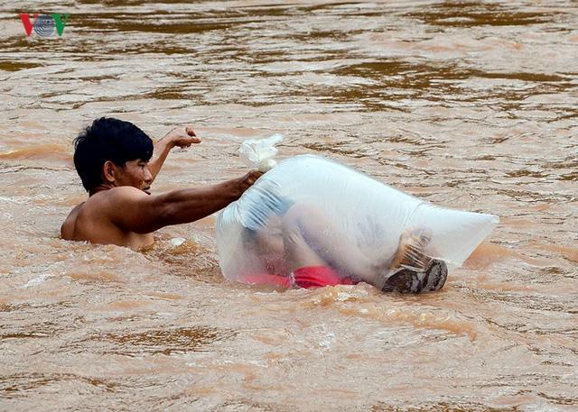 Học sinh chui vào túi nilon để người lớn đưa qua suối. (Ảnh: VOV)