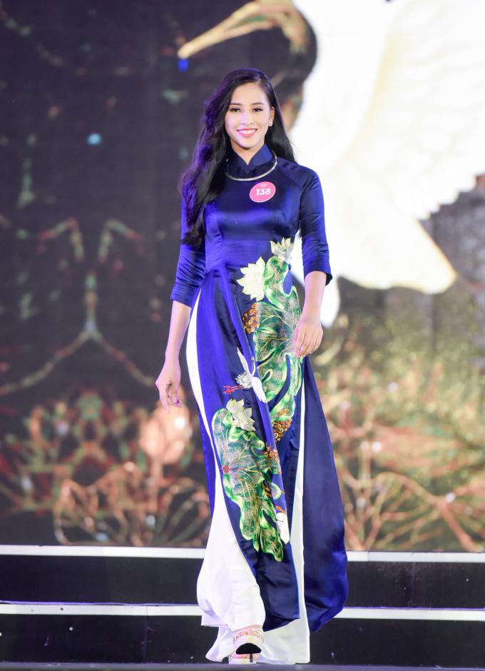 Trần Tiểu Vy thướt tha trong phần thi áo dài với trang phục họa tiết hoa sen nổi bật của nhà thiết kế Lan Hương, trên sân khấu thi chung khảo ở Nghệ An. So với những thí sinh cùng độ tuổi 18, vừa tốt nghiệp THPT, nhan sắc của Tiểu Vy được nhận xét chín muồi hơn.