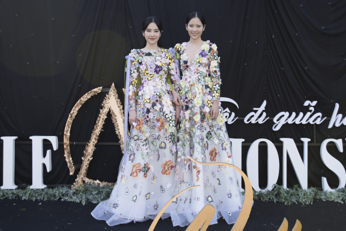 Hai chị em sinh đôi Nam Anh - Nam Em nằm trong số những khách mời gây chú ý tại khu vực thảm đỏ. Diện bộ váy hoa là mẫu thiết kế mới nhất của NTK Hằng Nguyễn, cả hai hóa thân thành hai nàng tiên lộng lẫy dạo bước trên thảm cỏ xanh mát chúc mừng show diễn sắp diễn ra.