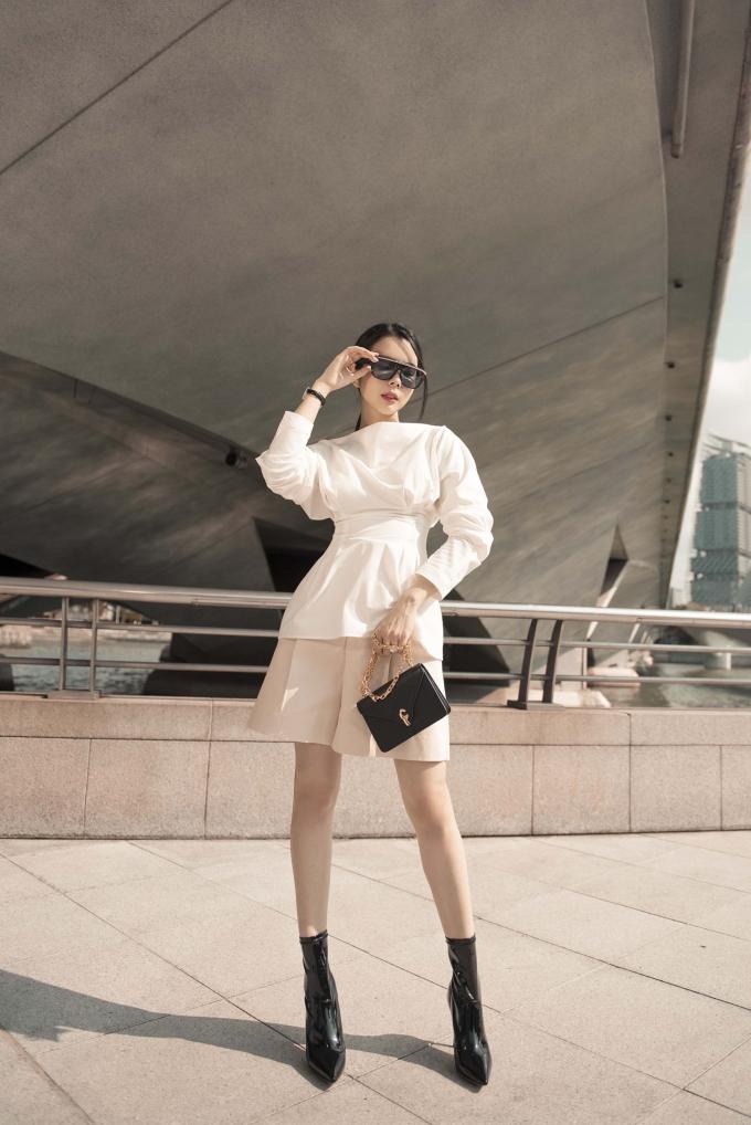 Trong set đồ này, cô tinh tế kết hợp một chiếc áo kiểu cách với phần bóp nhẹ ở eo cùng lớp bèo dúm nơi cổ tay kết hợp cùng chiếc quần đùi ống rộng có chút gì đó nữ tính và phóng khoáng.