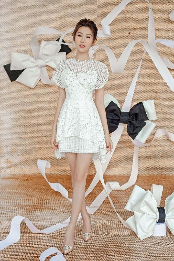 Cổ áo được thiết kế lưới cách điệu nhắc lại ở phần chân váy vô cùng tinh tế. Họa tiết hoa trên nền chất liệu ren cao cấp khiến bộ trang phục trở nên mềm mại.