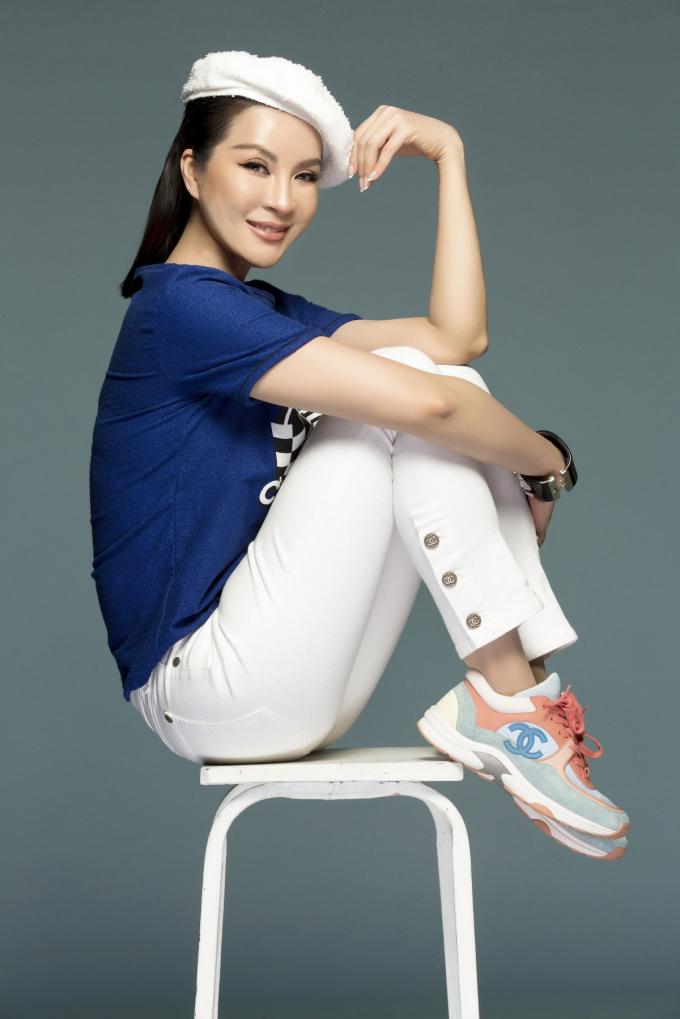 """Nữ MC """"Sức sống mới"""" giới thiệu phong cách thời trang xuống phố năng động. Người đẹp phối áo phông xanh có họa tiết với quần denim trắng. Sneaker cá tính, vòng tay to bản giúp tăng vẻ năng động."""