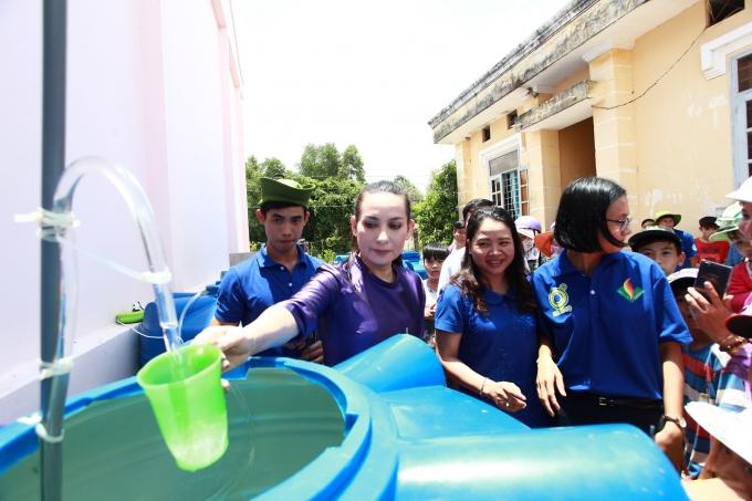 Phi Nhung hứng những giọt nước đầu tiên từ chiếc máy lọc nước.