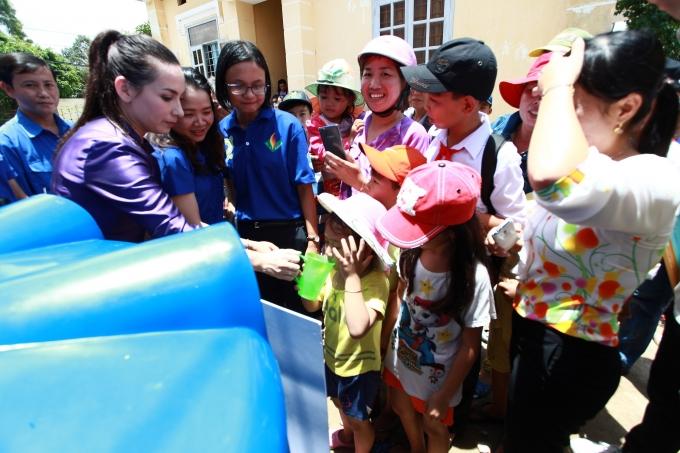 Phi Nhung đưa nước cho các em nhỏ và bà con nhân dân ở xã Hiệp Thạnh uống thử.