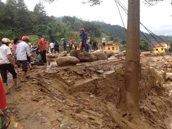 Nhân dân tập trung di chuyển đá do lũ để lại để lấy đường di chuyển.