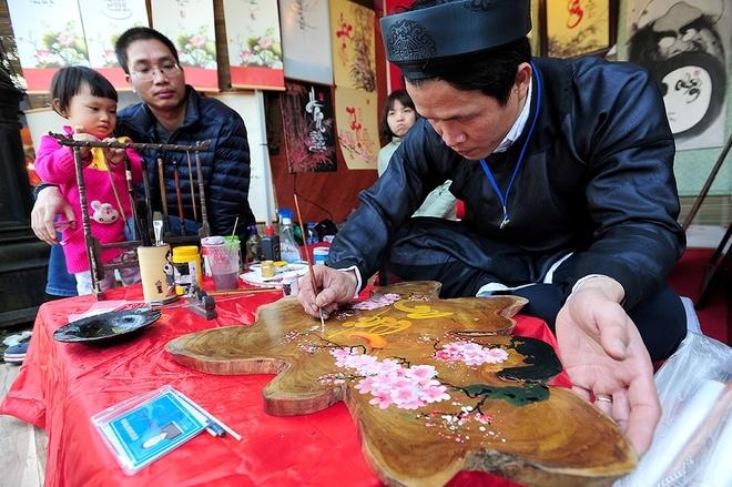 Thầy đồ Hoàng Xuân Thuỷ đang viết chữ Thái An với ý nghĩa bình an trong trong tâm trí. Thầy Thuỷ viết chữ trên vân gỗ bằng chất liệu acrylic.