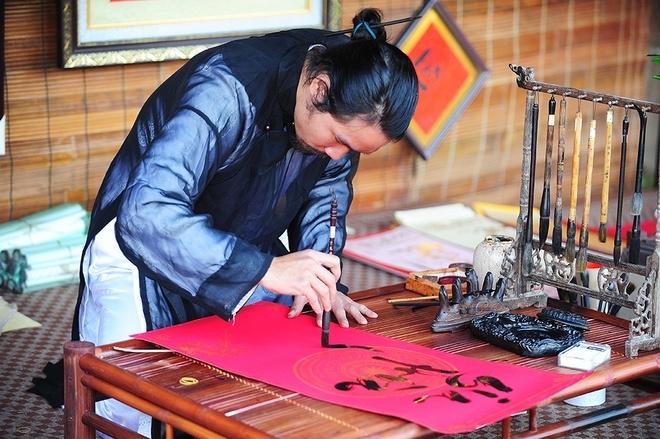 Hà Huy Long 28 tuổi, là hoạ sĩ, thích viết và đam mê thư pháp.                Thầy đồ Hoàng Xuân Thuỷ đang viết chữ Thái An với ý nghĩa bình an trong trong tâm trí. Thầy Thuỷ viết chữ trên vân gỗ bằng chất liệu acrylic.